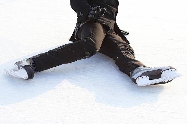 Pés de patins de um homem caído em uma pista de gelo