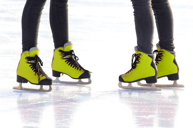 Pés de patins em uma pista de gelo. hobbies e recreação. esportes e feriados