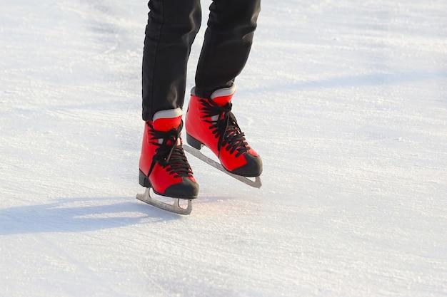 Pés de patins vermelhos em uma pista de gelo. esporte e entretenimento. descanso e férias de inverno
