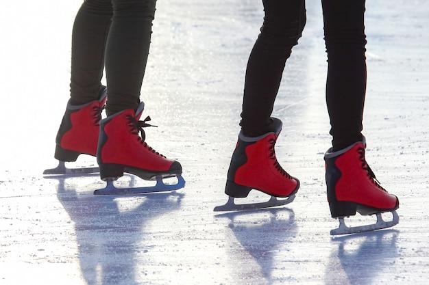 Pés de patins vermelhos em uma pista de gelo. esporte e entretenimento. descanso e férias de inverno.