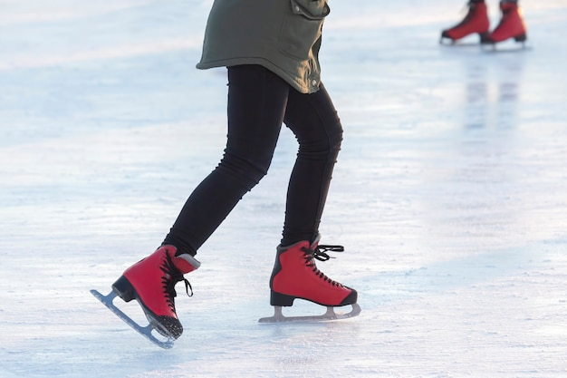Pés de patins vermelhos em uma pista de gelo. hobbies e esportes. férias e atividades de inverno.