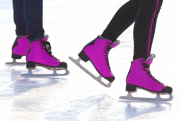 Pés de patins vermelhos em uma pista de gelo. hobbies e recreação. esportes e feriados