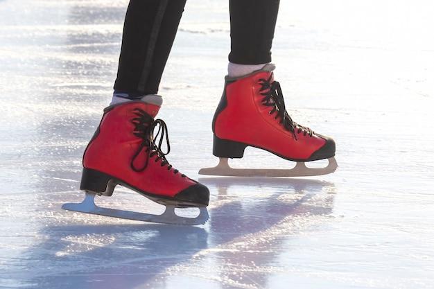 Pés de patins vermelhos em uma pista de gelo. passatempos e lazer. esportes de inverno