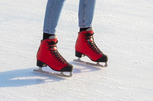 Pés de patins vermelhos em uma pista de gelo. passatempos e lazer. esportes de inverno Foto Premium