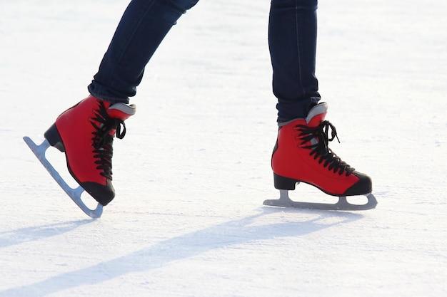 Pés de patins vermelhos em uma pista de gelo