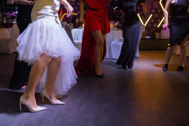 Pés de pessoas dançando em uma festa de clube irreconhecíveis