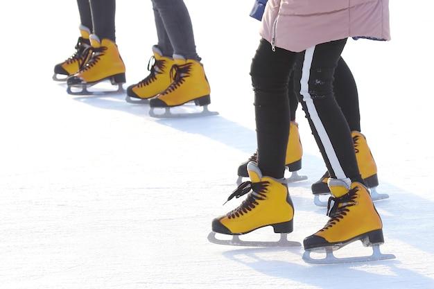 Pés de pessoas patinando em uma pista de gelo de rua. esporte e entretenimento. descanso e férias de inverno.