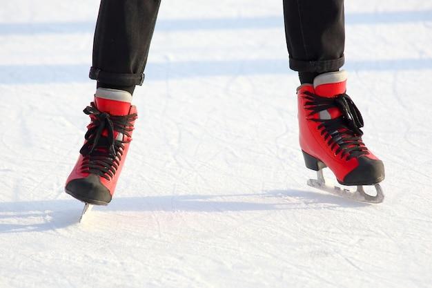 Pés de pessoas patinando em uma pista de gelo de rua