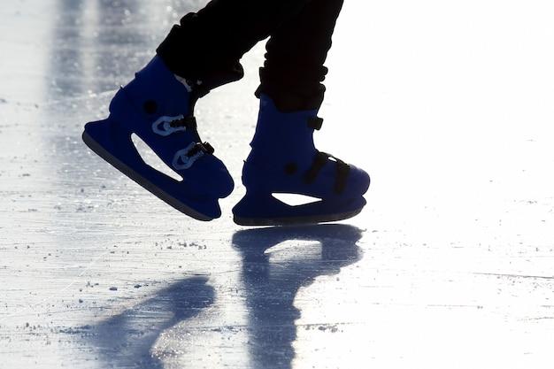 Pés de pessoas patinando na pista de gelo