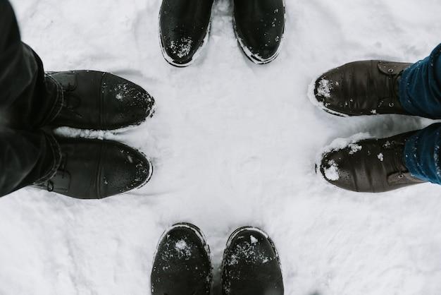 Pés de quatro pessoas na neve, close-up