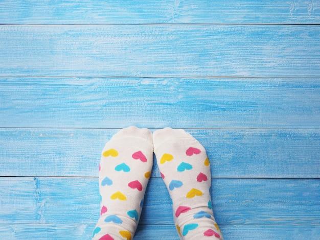 Pés de selfie usando meias brancas com padrão de forma de coração pastel no fundo do assoalho de madeira azul e espaço de cópia. estilos de vida modernos.