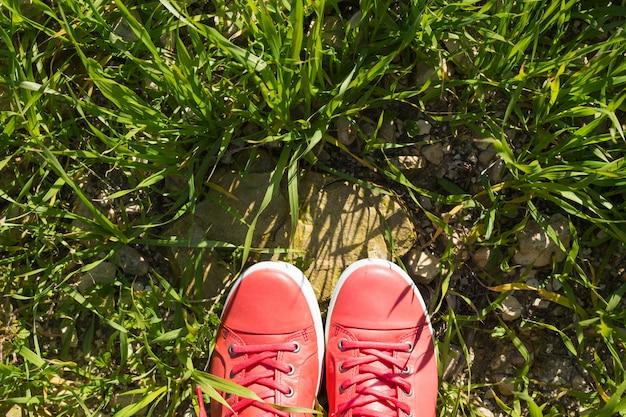 Pés de tênis rosa na grama verde