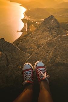 Pés de tênis vermelhos em um penhasco íngreme com vista para a paisagem do pôr do sol com o mar e as montanhas