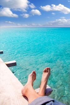 Pés de turista turquesa de praia relaxada no cais tropical
