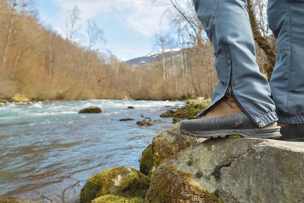 Pés de um alpinista usando tênis de caminhada em uma rocha acima de um rio alpino que flui em um vale