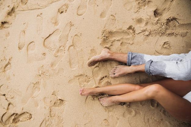 Pés de um casal apaixonado deitado na areia vista de cima