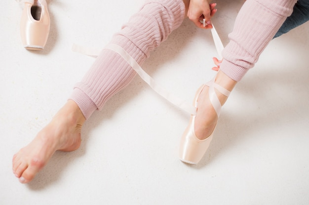 Pés de um close-up da bailarina em um fundo branco de cima de. bailarina coloca sapatilhas.