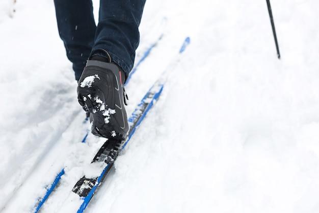 Pés de um esquiador com botas de esqui em esquis cross-country na neve