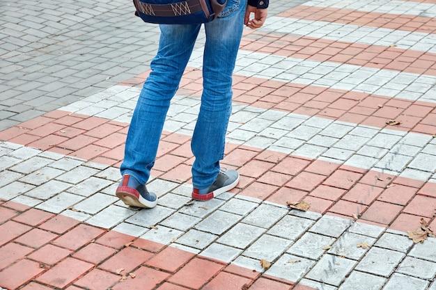 Pés de um homem caminhando em uma faixa de pedestres em um parque da cidade