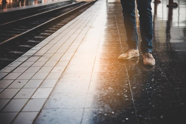 Pés de um jovem com jeans que aguarda o trem na plataforma da estação de trem.