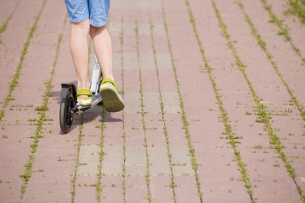 Pés de uma criança menino com tênis na scooter em um dia ensolarado