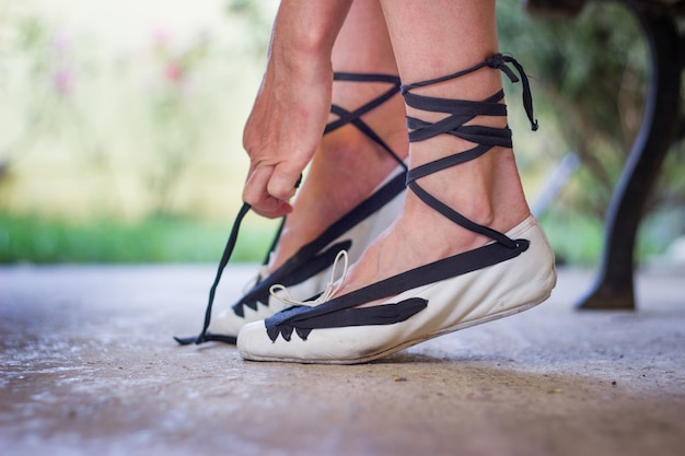 Pés de uma dançarina amarrando os sapatos