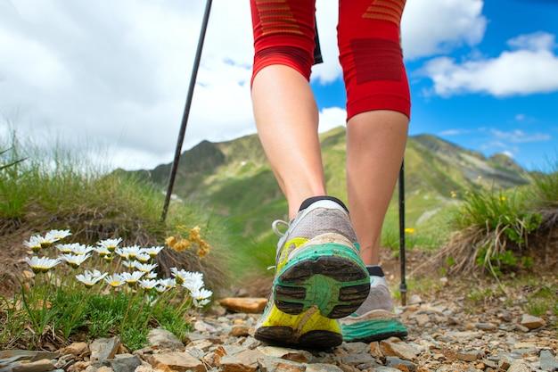 Pés de uma mulher que caminha nas montanhas com bengalas nórdicas
