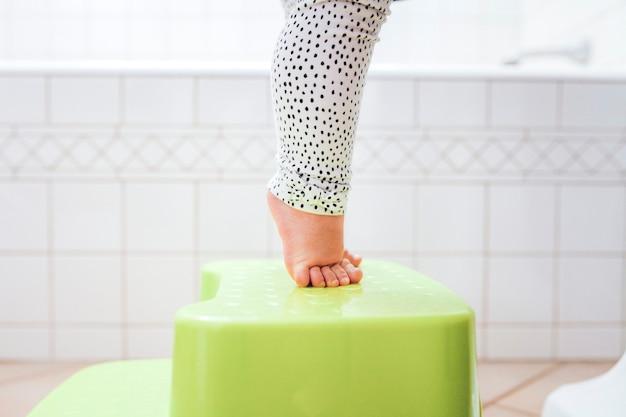 Pés descalços da criança na ponta dos pés no banquinho