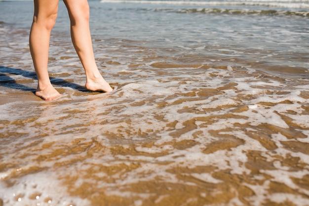 Pés descalços da mulher na água do mar rasa na praia