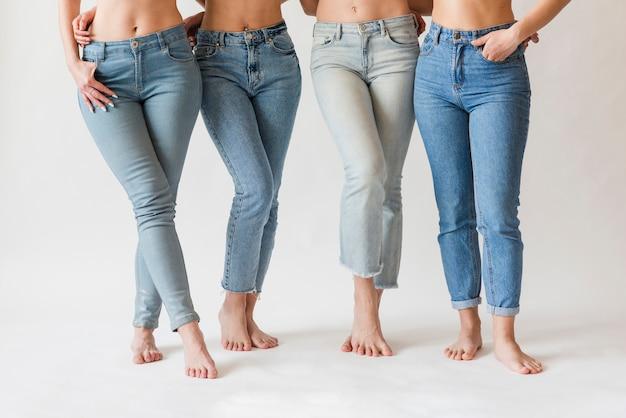 Pés descalços de grupo feminino em jeans