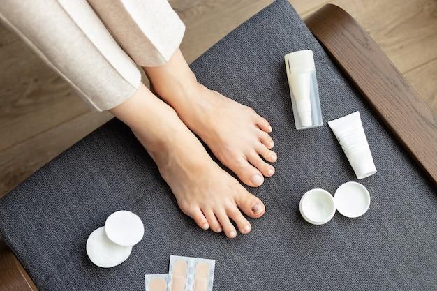 Pés descalços de mulher com lesão na unha e kit de ajuda médica.