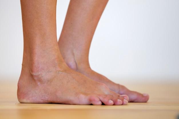 Pés descalços de mulher no chão