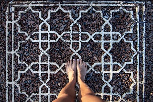Pés descalços de mulheres em uma superfície de pequenas pedras