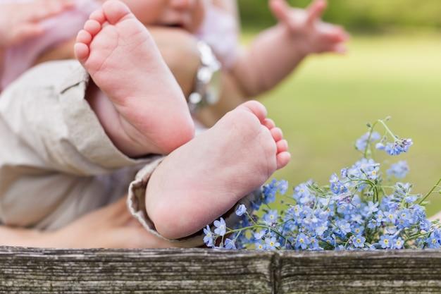 Pés descalços de um bebê fofo e não se esqueça de flores no fundo de madeira e uma criança