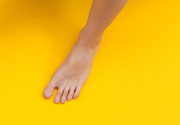 Pés descalços femininos em fundo amarelo. conceito de cuidados de beleza