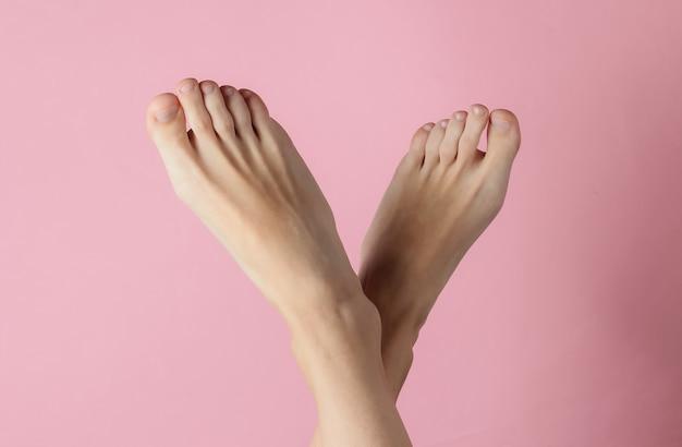 Pés descalços femininos em fundo rosa pastel
