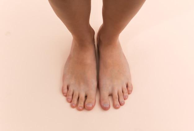 Pés descalços femininos em um fundo bege. conceito de cuidados de beleza