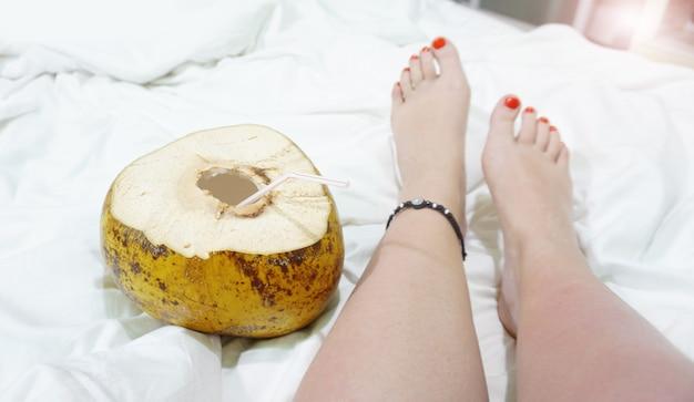Pés descalços femininos em um lençol branco, vista superior, close up. coquetel de coco perto dos pés. hotel à beira-mar