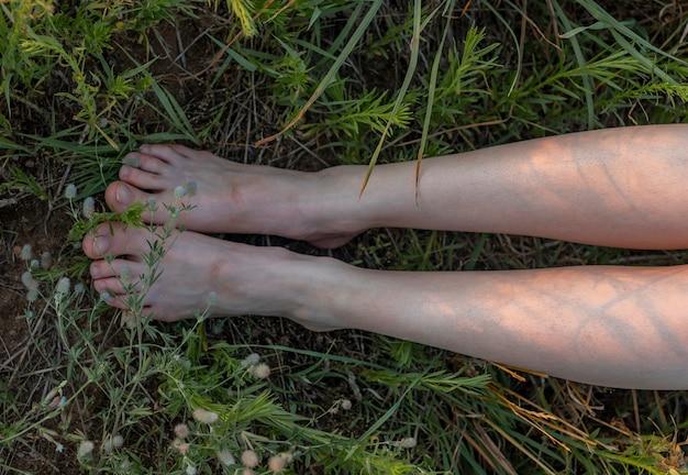 Pés descalços femininos pernas estreitas em vista de cima da grama