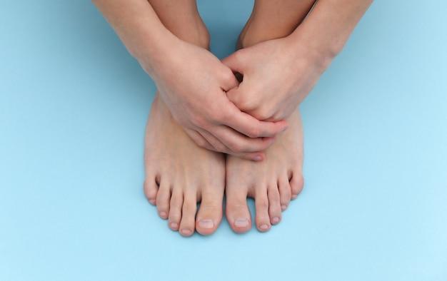 Pés descalços femininos sobre fundo azul. conceito de cuidados de beleza