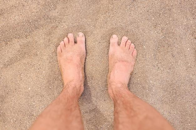Pés descalços masculinos na areia quente da praia, closeup