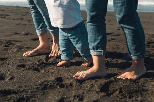 Pés do bebê e pais caminhando na costa arenosa