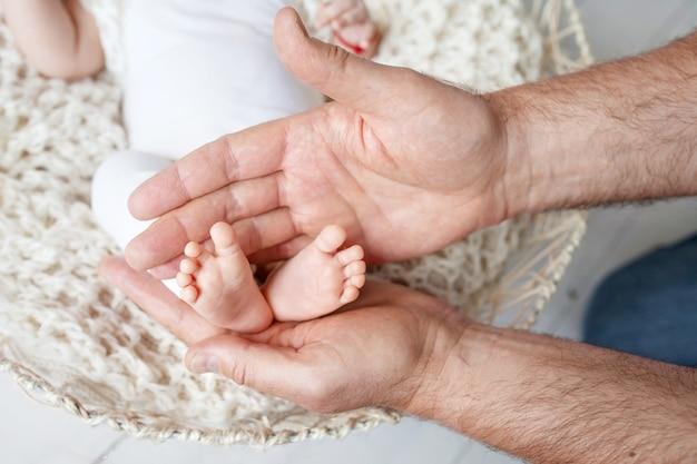 Pés do bebê nas mãos do pai.