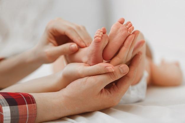 Pés do bebê recém-nascido na palma da mãe em fundo branco