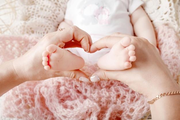 Pés do bebê recém-nascido nas mãos da mãe, a forma de um lindo coração. mãe segurando as pernas da criança nas mãos. feche a imagem. família feliz