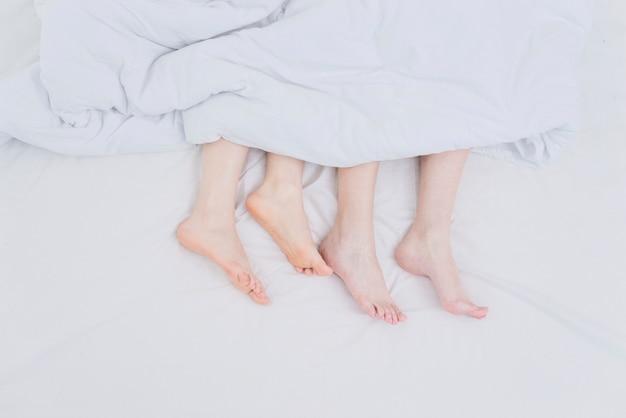 Pés do casal de lésbicas fora do cobertor sobre a cama
