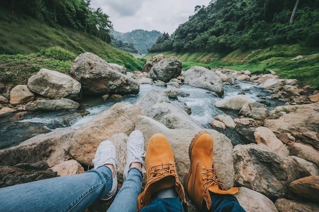 Pés do casal relaxando enquanto está sentado olhando a vista do rio da montanha