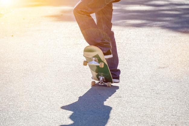 Pés do close up do adolescente que jogam um skate na estrada do parque público.