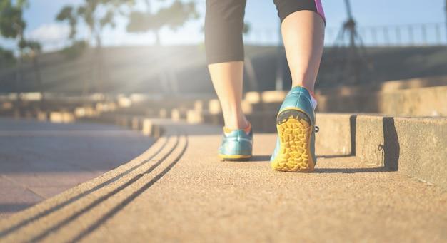 Pés do corredor da mulher da aptidão no foco da trilha na sapata do esporte. conceito de bem-estar de fitness e treino.