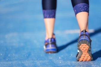 Pés do corredor que correm o close up na sapata. mulher fitness jog treino welness conceito.